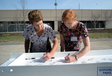 Registered nurses Linda Marks, left, and Maureen Shaughnessy-Toy sign the final structural beam for the new lobby at Lehigh Valley Hospital in Salisbury Township before the beam is hoisted into place.