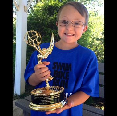 "Owen Miller, a three-time participant in the ""Tri for Inclusion,"" is shown in with eMediaWorkshop's Mid-Atlantic Region Emmy award. The production company won the Emmy for promotion-news and public service announcement-single spot Sept. 19, 2015, in Philadelphia for a video on the triathlon for children with disabilities started in 2013. (Courtesy photo 