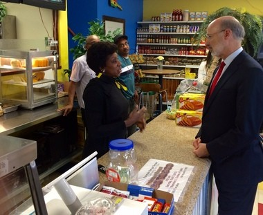 Pennsylvania Gov. Tom Wolf, right, speaks Thursday afternoon with Parkway Caribbean owner Rose Thomas, left, at her restaurant, 209 W. Union St. in Allentown, during his tour to push to increase the state's minimum wage. (Sarah Cassi   lehighalleylive.com)