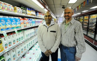 Rocky Patel owns the Portland Market, which is holding a ribbon cutting Sunday. Duane Smith, right, is the market manager.