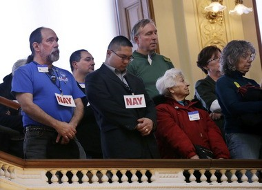 Members of the gallery today in the New Jersey Statehouse in Trenton wear tags urging votes against gun control laws being taken up by the Assembly.