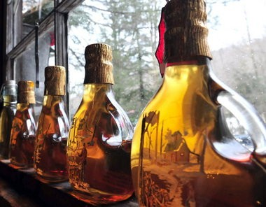 Maple syrup is displayed in glass bottles. A new grading system for the syrup is being used for this year's production.