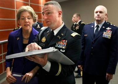 U.S. Sen.-elect Elizabeth Warren, D-Mass., left, confers with Mass. Army National Guard Lt. Col. Thomas Stewart, center, moments before ceremonies held to commemorate the opening of the Mass. National Guard Joint Force Headquarters at Hanscom Air Force Base Thursday.. The ceremonies also celebrated the 376th birthday of the National Guard. Maj. Gen. L. Scott Rice, The Adjutant General, Mass. National Guard, looks on at right.