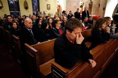 Mourners gather for a vigil service for victims of the Sandy Hook Elementary School shooting at St. Rose of Lima Roman Catholic Church in Newtown, Conn., on Friday. A man killed his mother at their home and then opened fire Friday inside the elementary school, massacring 26 people, including 20 children.