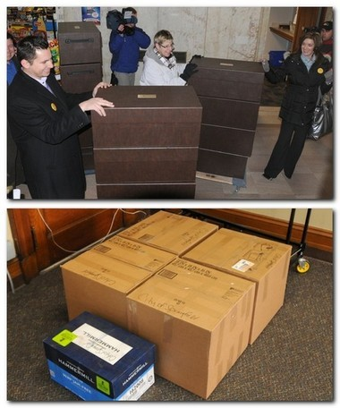 Above, employees of MGM Resorts wait to board the elevator in City Hall as they deliver 18 boxes containing their casino proposal to the city's Procurement Office on Thursday morning. Below, boxes with the Penn National Gaming casino proposal sit in the Procurement Department.