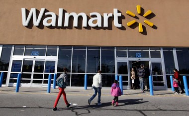 In this Feb. 20, 2012, file photo, customers walk into and out of a Walmart store in Methuen, Mass.