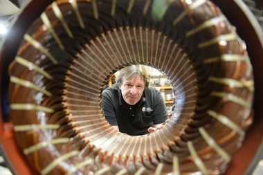 David Manning, CEO of Applied Dynamics in Greenfield, looks through the windings of one of the large industrial electric motors rebuilt at his company.