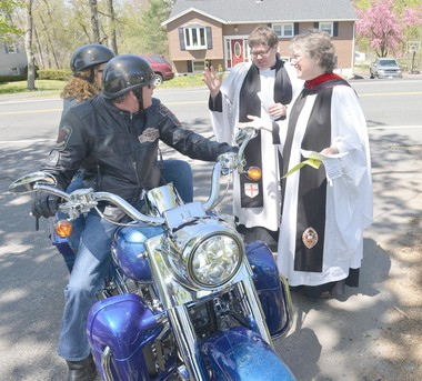 WILBRAHAM- The Rev. Peter Swarr, with St. Mark's Episcopal Church in East Longmeadow and The Rev. Meredyth Wessman Ward with the Episcopal Church of the Epiphany in Wilbraham bless Steve and Colette Iampietro's Harley Davidson at the first Blessing of the Bikes at Fountain Park. The Iampietro's live in Wilbraham.
