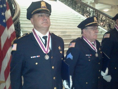 Acting Chicopee Police Chief Thomas Charette, left, and Chicopee Sgt. Roy Landry, right, stand in line to receive awards for police bravery at the Statehouse.
