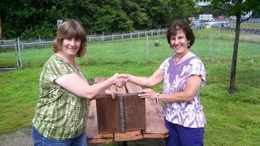 Debbi Scheetz left presenting the 80-pound steel piece from the World Trade Center Tower to Cindy Wloch