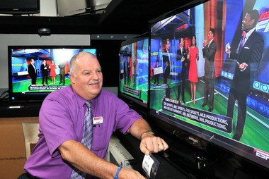 In this file photo, Daniel L. Evans, salesman at Manny's TV and Appliance on Boston Road in Wilbraham, looks over one of the many TV's that were available during a sales tax holiday in 2011.