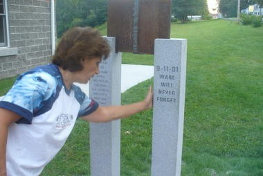 9/11 Memorial being erected at Ware Fire Station. Cindy Wloch, wife of deputy fire chief Ed Wloch is inspecting the recently completed granite work. An 80 pound piece of steel from a steel beam from one of the World Trade Center buildings that was destroyed on September 11, 2001 is shown hung between the two granite pieces.