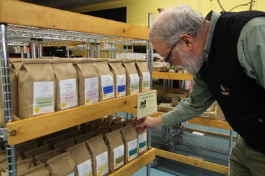 Al Sax, general manager of the Amherst coop All Things Local, adjusts some bags of locally grown flour. The store recently opened in downtown Amherst.