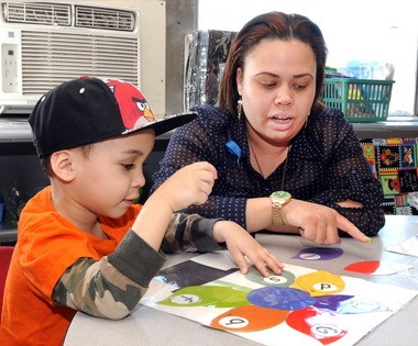 Tahirah Graham, right, a teacher at the Holyoke Chicopee Springfield Head Start pre-school, works with Justin Pena in her class. The state is expanding criminal background checks for all teachers to protect children of all ages.