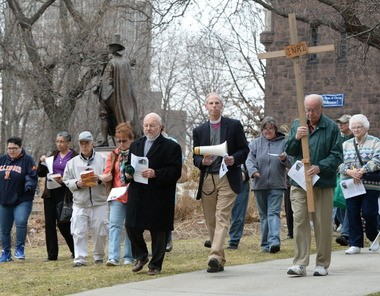 Christ Church Cathedral held a Way of the Cross procession led by then cathedral Dean James Munroe and Episcopal Bishop Douglas J. Fisher, center, on Good Friday in 2015. Here they walk to their next stop along State Street in Springfield.