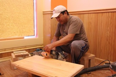 Karma Tsering sands a bench that will be part of the furniture at the new Himalayan restaurant in Amherst. The owners are doing all the work themselves.