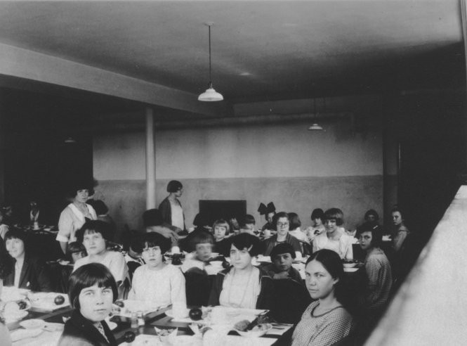 This photo shows dinner being served in one of the women's buildings at the Belchertown State School in the late 1920s or early 1930s. Food was prepared for residents at a central kitchen and delivered to the various dormitories. Note the Buster Brown haircuts on most of the women--the preferred style because it was said to be easier for the staff to do than anything else. (Photo courtesy of the Clapp Memorial Library)
