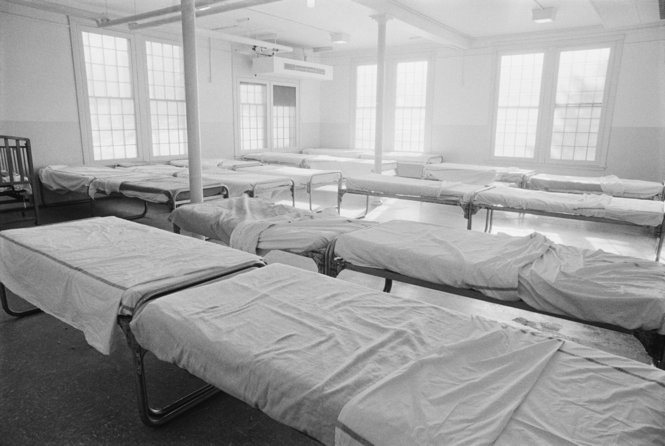 In this 1972 photo, empty beds at the Belchertown State School are pictured. James Shanks reported in his 1970 expose on the conditions at Belchertown State School where men slept in large barracks, beds touching head to foot, with only a narrow twelve-inch aisle separating rows. Sometimes residents had to climb over one another to get to and from their beds. (Photo courtesy of Jeff Albertson/CORBIS)