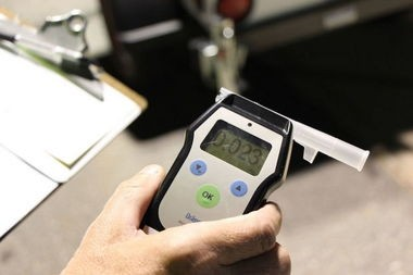 A Massachusetts State Police trooper shows a preliminary breath tester displaying the results of a test on a driver during a sobriety checkpoint in April 2015.