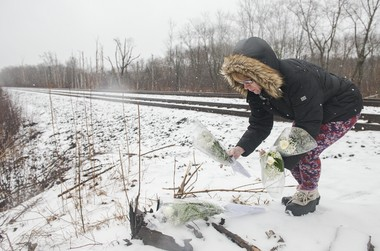 On April 1, 2017, Laurie L. Roberts of Ludlow places flowers near the Longmeadow railroad crossing where her uncle, Warren P. Cowles, was killed in a March 14 collision with a train.