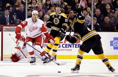 Boston Bruins defenseman Torey Krug tees up for a shot with Zdeno Chara in front against the Detroit Red Wings.