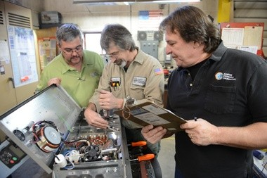David Manning, CEO of Applied Dynamics (right) looks over variable speed motor control board with tech Paul Williams (center) and Company VP Dave Cunningham (left)
