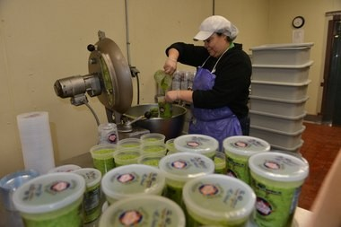 Latino Food Distributors employee Daisy Trujillo fills containers of sofrito in one of the mixing rooms at the West Springfield facility.