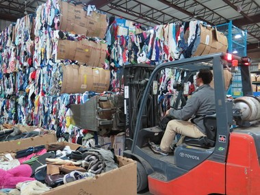 Jarrid Kendall, Salvation Army production supervisor, uses a forklift to stack bales of recycled textiles at the Springfield facility.