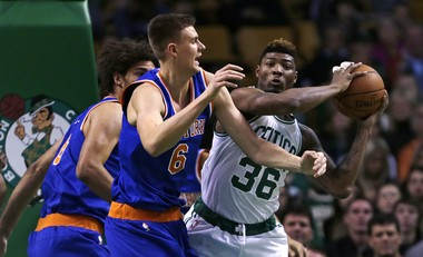 Boston Celtics guard Marcus Smart (36) grabs a rebound as he is pressured by New York Knicks forward Kristaps Porzingis, of Latvia, (6) during the first quarter of a preseason NBA basketball game in Boston, Thursday, Oct. 22, 2015.