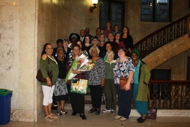 Con flores en manos, Maria Luisa Arroyo rodeada de sus amistades y familiares el dia de la proclamacion comola primera Poeta Laureado de Springfield.