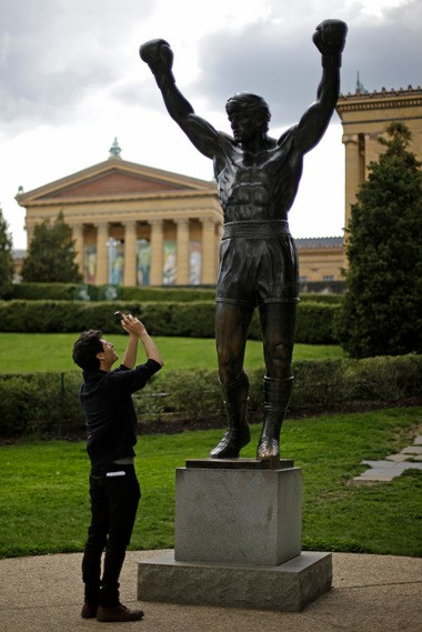 A tourist photographs a bronze Rocky statue outside the Philadelphia Museum in Philadelphia.