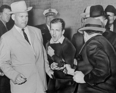 Lee Harvey Oswald, accused assassin of President John F. Kennedy, reacts as Dallas night club owner Jack Ruby, foreground, shoots at him from point blank range in a corridor of Dallas police headquarters, in this Nov. 24, 1963 file photo. Plainclothesman at left is Jim A. Leavelle. (AP photo)