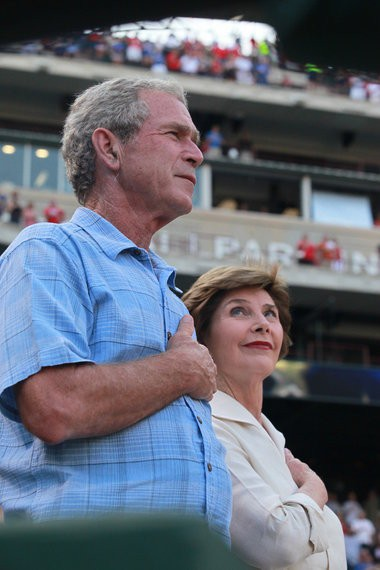 Former President George W. Bush and Laura Bush stand for the National Anthem before the first inning of a baseball game between the Texas Rangers and the Oakland Athletics, Thursday, July 7, 2011, in Arlington, Texas. (AP Photo/Jeffery Washington)