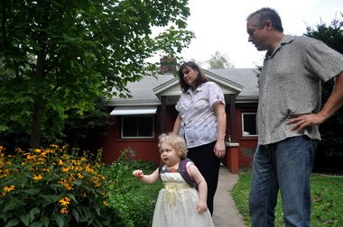 Rowan Baker, 3, and her mother Rebecca Paniagua and father Chuck Baker pick a bundle of flowers from their garden at their home in Monson in this file photo.