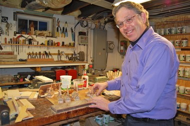 David C. Furlong shows some wooden churches he is in the process of making in the basement workshop of his Sunderland home. He makes a variety of designs including barns, a train station, a schoolhouse, houses, a sugar house and a covered bridge.