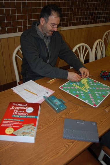 Ben L. Greenwood of the Florence section of Northampton places a word on the Scrabble board.