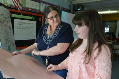 History teacher Deborah Hart looks over a mural project worked on by Siobhan Brennan, a seventh-grader, who helped found the after school history club.
