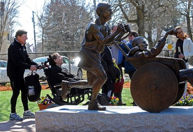 Dick Hoyt, left, pushes his son Rick past their statue to a waiting van after the statue was dedicated in their honor in front of Center School in Hopkinton.