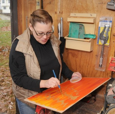 Kari LeBeau works on the painting end of the product.
