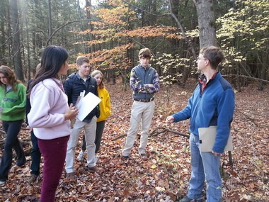 Joshua W. Morse, Franklin Land Trust assistant land steward, talks with Deerfield Academy students about identifying invasive plants.