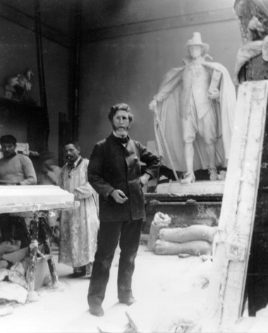 "Augustus Saint-Gaudens in his Paris studio in 1898 with the cast for his statue, ""The Puritan,"" behind him."