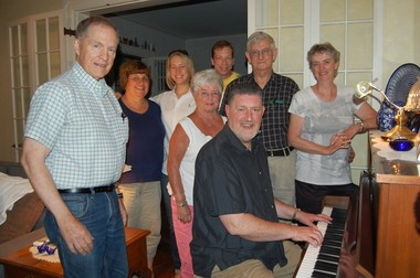 Paul J. Calcari (seated), director of The Franklin County Community Chorus, gathers at the piano at his Greenfield home with members of the chorus.