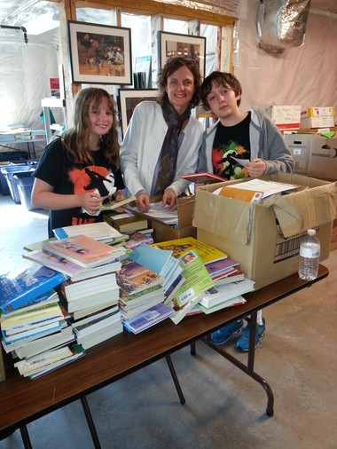 Christine Mirot, of Longmeadow, is shown here with her daughter, Abby, 11, and son, Ranen, 13, volunteering at Link to Libraries. Ranen Mirot completed a community service project Ranen did for his bar mitzvah by organized a book drive for Link to Libraries.