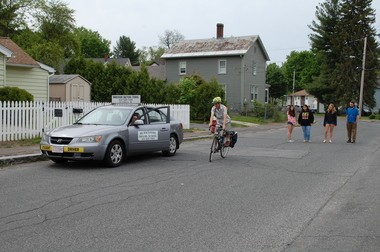 Ruthy M. Woodring, a worker-owner of Pedal People Cooperative, rides her bike past Mariah F. Blaney, owner of Berkshire Driving School in Easthampton, as she opens the car door. Driving school students watch the demonstration with Brett I. Constantine, one of the Pedal People instructors.