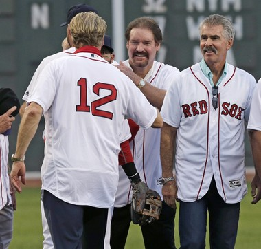 Former Boston Red Sox third baseman Wade Boggs, center, and first baseman Bill Buckner, right, joke with Steve Lyons (12) as they are honored with their 1986 baseball teammates prior to a baseball game against the Colorado Rockies in Boston, in May of this year. The Red Sox won the 1986 American League Championship, before losing to the New York Mets in the World Series.