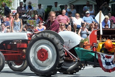 In this file photo from July 4, 2011, Russell J. Peotter, WGBY general manager and a town resident, drives a tractor pulling a float in the annual Independence Day parade in Chesterfield.