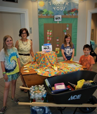 Children's librarian Jean Maziarz and three summer reading program participants stand beside the summer community service display in the lobby at Storrs Library in Longmeadow. This summer the library is collecting items for Gardening the Community, a food justice organization in Springfield. Library patrons, both children and adults, can purchase needed items for the food nonprofit, or children can donate their earned play money toward purchasing fruit trees. Left to right: Florine Mulcahy, 11, Maziarz, Clementine Mulcahy, 11, and Miles Haag, 5.