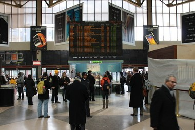 Boston area commuters wait inside South Station to see which track their train will depart on.
