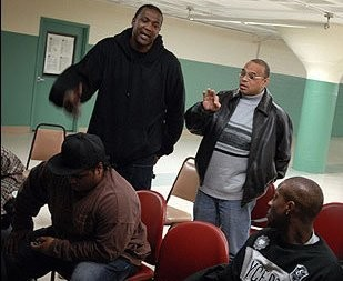 """In this 2009 photo posted to Shaun Harrison's Facebook page, Harrison, standing at right and wearing a black leather jacket, gives a """"gang talk"""" at the Tobin Community Center in Boston's Roxbury neighborhood. Harrison, a minister and educator who attended Springfield College, has been charged with shooting a teenager whom he had enlisted to sell drugs for him, according to police and prosecutors. (FACEBOOK)"""