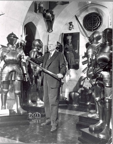 John Woodman Higgins bends a sword among suits of armor in his museum's Great Hall in 1951